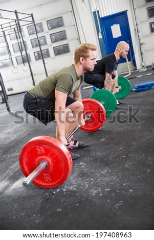 Two men train deadlift at fitness gym center - stock photo