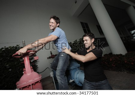 Two men trying to turn off the water - stock photo