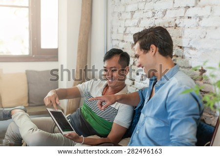 Two Men Using Tablet Computer Internet at Cafe, Asian Mix Race Friends Guys Sitting at Cafe Natural Light - stock photo