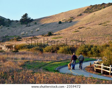 Two men walk with a dog on a nature path through Pacifica's quarry. - stock photo