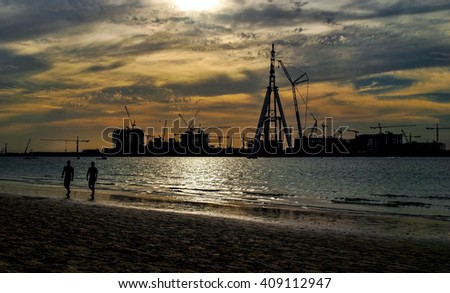 Two men walking along the beach against the background of the Dubai Eye construction. Sea skyline. Sunset. Quiet harbor. - stock photo