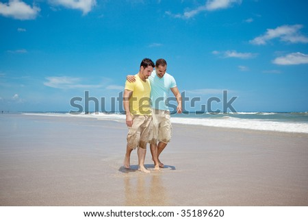Two men walking on a beach - stock photo