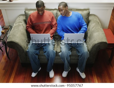 Two men with laptops on couch - stock photo