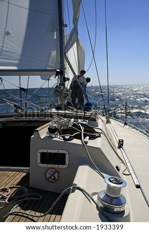 Two men work with sails.  Aboard a beautiful yacht there is a rigging, cords and blocks. - stock photo
