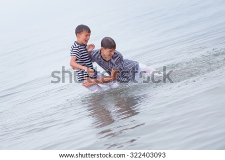 Two merry, happy, brother plays at sea, laughing and squirting water, italy,  - stock photo
