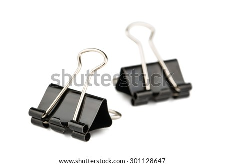 Two metal paper binder clips isolated on white background. A distant binder clip is blurred. - stock photo