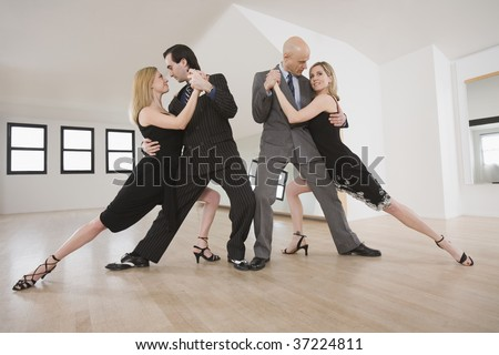 Two mid adult couples dancing Argentine Tango - stock photo