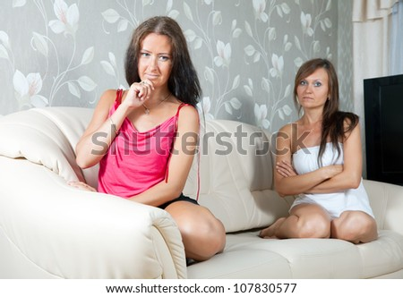 Two mid adult women after quarrel at home - stock photo