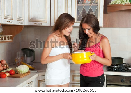 Two mid adult women cooking at them kitchen - stock photo