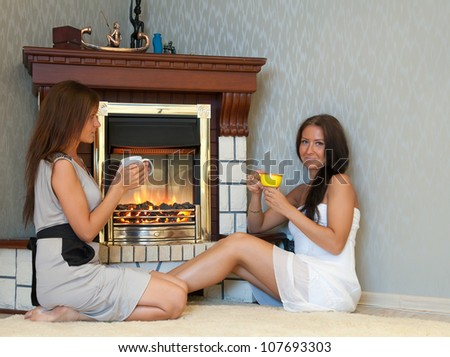 Two mid adult women near the  electric fire - stock photo