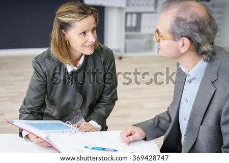 two middle-aged colleagues working on documents in the office - stock photo