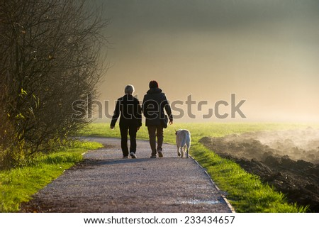 Two middle aged women walking a dog on a path in a park. - stock photo
