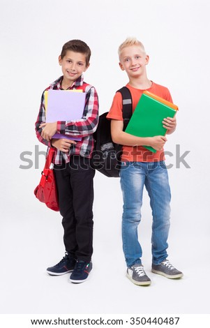 Two mischievous cheerful schoolboy with books in their hands and backpacks on a white background laughing. - stock photo