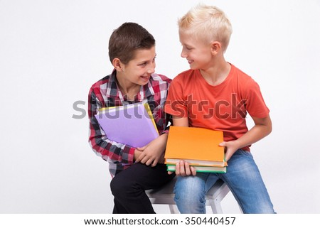 Two mischievous cheerful student with books in hand on white background laughing - stock photo
