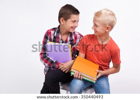 Two mischievous cheerful student with books in hand on white background laughing. - stock photo