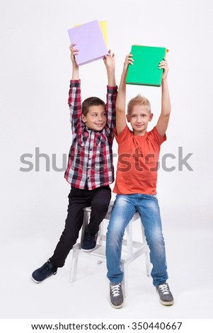 Two mischievous cheerful student with books in hand on white background laughing hands up. - stock photo