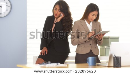 Two mixed race colleagues talking on mobilephone and using tablet - stock photo