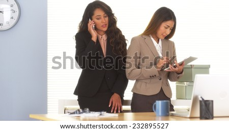 Two mixed race colleagues talking on smartphone and using tablet - stock photo