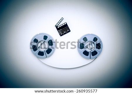 Two 8mm blue reels horizontally connected with film and a little clapper board vintage color effect - stock photo
