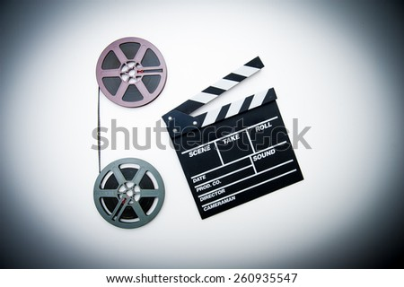Two 8mm purple and grey movie reels vertically connected with film and clapper board in vintage color effect - stock photo