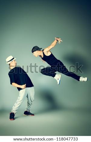 Two modern dancers dancing hip-hop at studio. - stock photo