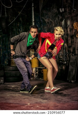 Two modern dancers dancing in the garage. Urban lifestyle. Hip-hop generation. - stock photo