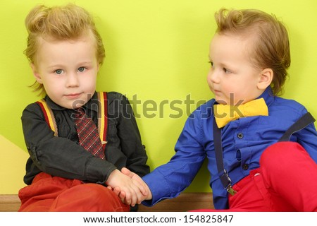 Two mods boy in bright clothes with stylish hairstyles shake hands - stock photo