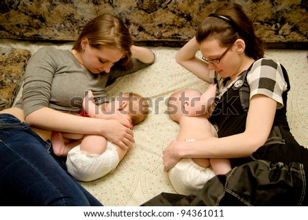 Two mothers at the same time breastfeeding lying on the bed - stock photo