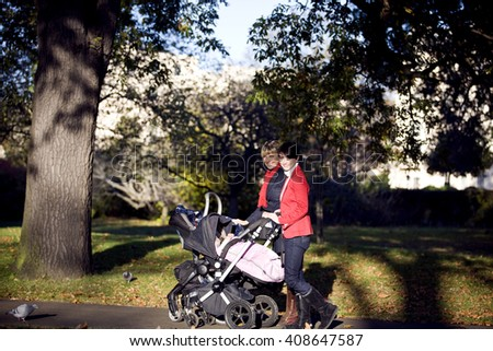 Two mothers pushing their strollers in the park, smiling - stock photo