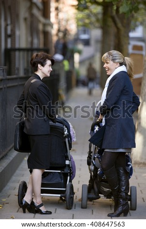 Two mothers pushing their strollers, talking - stock photo