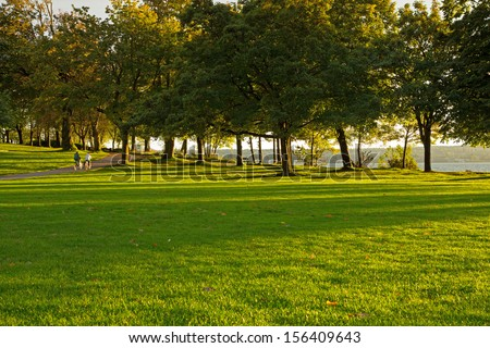 Two motion blurred bicyclists riding at sunset in Stanley Park - stock photo