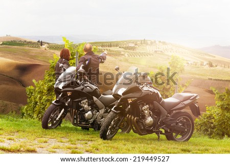 Two motorcyclists enjoying the view in Tuscany - stock photo