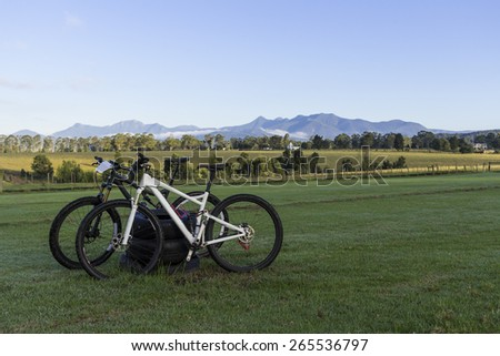 Two mountain bikes in the foreground, mountain range in the background. - stock photo