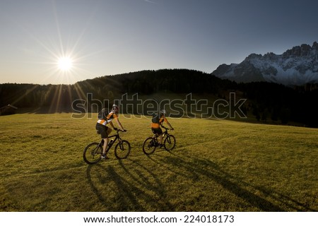 two mountainbikers in her shadow - mountainbike - stock photo