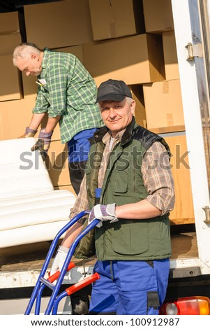 Two movers man loading furniture and boxes from truck vehicle - stock photo