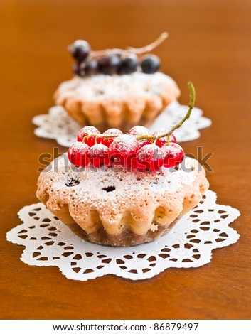 Two muffins and currants on wooden background - stock photo
