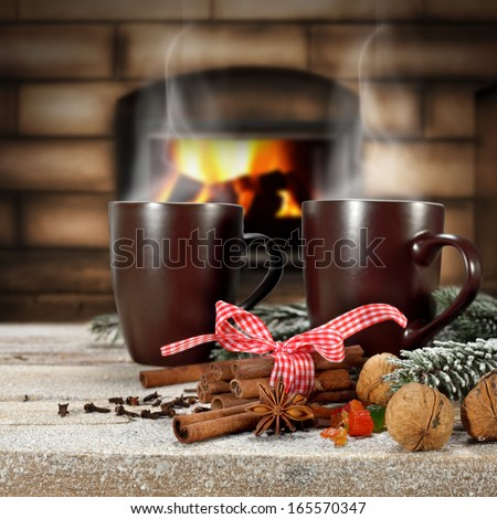 two mugs of brown and fireplace  - stock photo