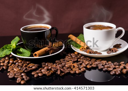 Two Mugs of Steaming Hot Cups of Coffee Garnished with Fresh Mint, Cinnamon Sticks and Star Anise on Black Surface Scattered with Roasted Coffee Beans - stock photo