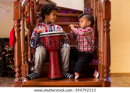 Two mulatto boys playing music. Kids play music on Christmas. Keep the rhythm, brother. Almost as skillful as me. - stock photo