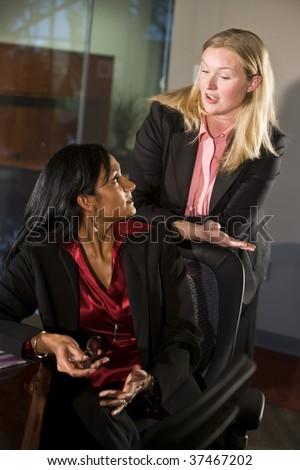 Two multi-ethnic businesswomen conversing in boardroom - stock photo