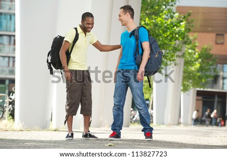 Two multicultural students laughing outdoors. Full body portrait of young African American and Caucasian students smiling. - stock photo