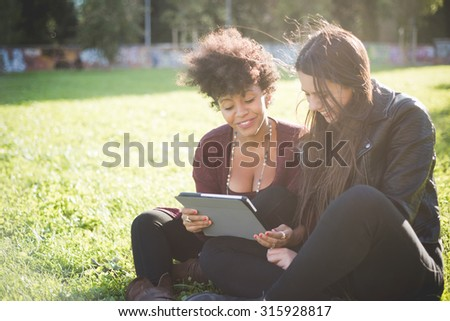 two multiethnic beautiful young woman black and caucasian sitting in a park using tablet, looking downward the screen, smiling - technology, communication, social network concept - stock photo