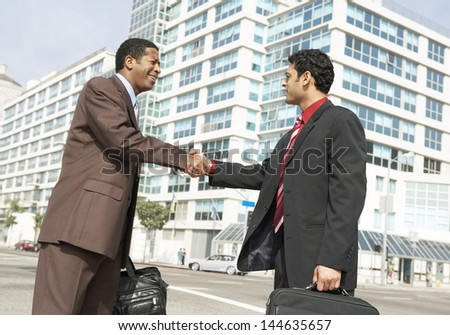 Two multiethnic business men shaking hands against buildings on city street - stock photo