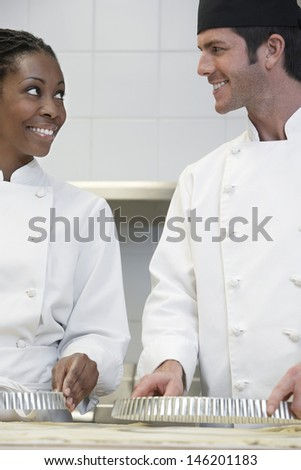 Two multiethnic chefs preparing food in kitchen - stock photo