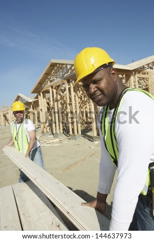 Two multiethnic construction workers stacking timber at site - stock photo