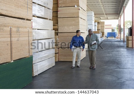 Two multiethnic men with clipboards walking along stacks of wood in warehouse - stock photo