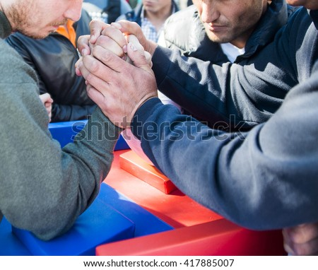 Two muscular hands clasped arm wrestling. no faces. on urban street.  - stock photo