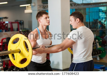 Two muscular young man working out in the gym - stock photo