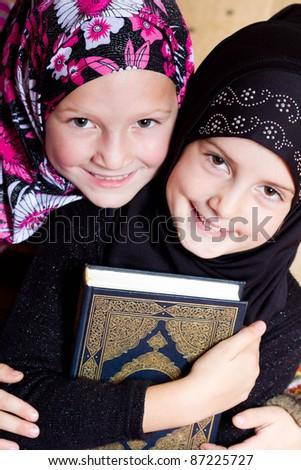 Two muslim girls holding Holy Book Koran - stock photo