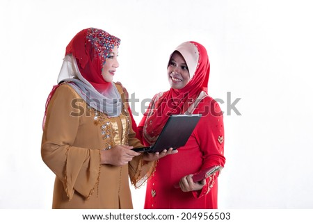 Two Muslim ladies in head scarf looking at each other while holding an electronic device each. - stock photo